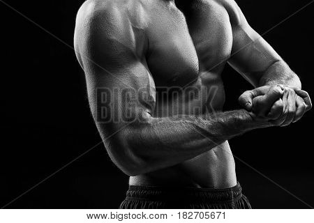 The colorless image of torso of attractive male body builder on black studio background.