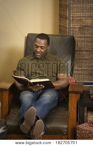 African man reading a book in armchair