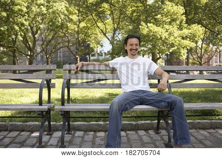 Mixed race man smiling on park bench