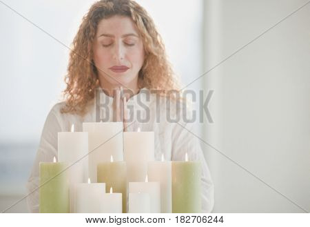 Hispanic woman praying by candles