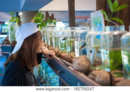 A young woman travelerwatching a Fighting Fish in Bottles at Siamese Fighting Fish Gallery Thailand