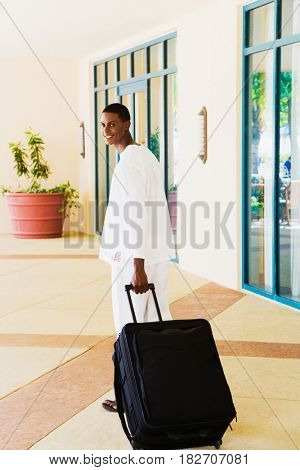 African man pulling suitcase