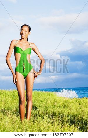 African woman in bathing suit with ocean in background