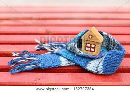 Small wooden house with window in a warm blue scarf on the red surface / real estate insurance