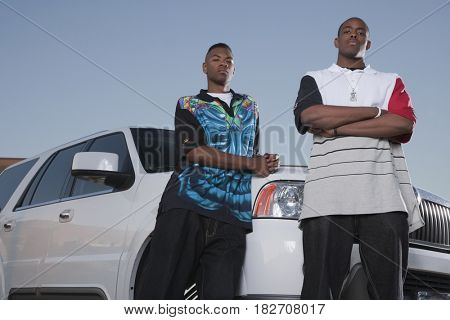 Serious African men leaning against sport utility vehicle