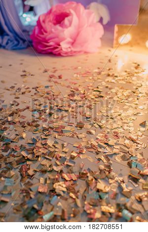 decoration of the birthday festive tinsel on the floor with lights and paper rose