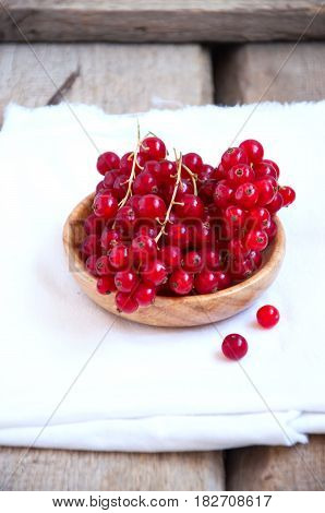 Heap Of Fresh Ripe Raw Red Currants In A Small Wooden Plate On A White Napkins. Rustic Style And Cop