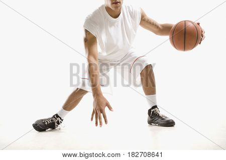 Mixed race basketball player dribbling ball