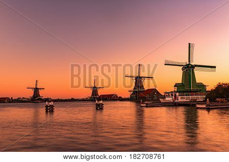 Magic orange lights at Traditional Dutch windmills in Zaanse Schans in sunrise time Amsterdam area Holland