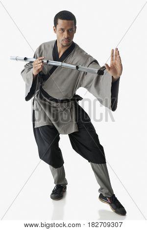 Mixed race martial artist holding stick