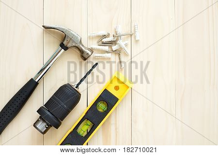 Drill and hammer levels and screw on wooden background for DIY concepts