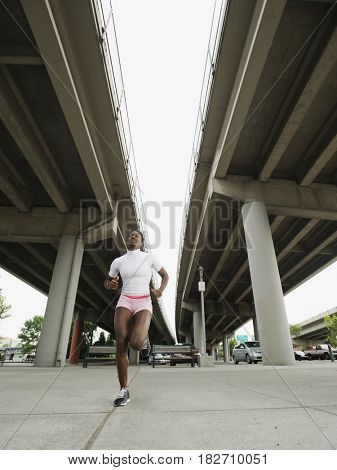 African woman running under freeway overpass