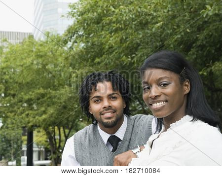 Businessman and businesswoman smiling in park