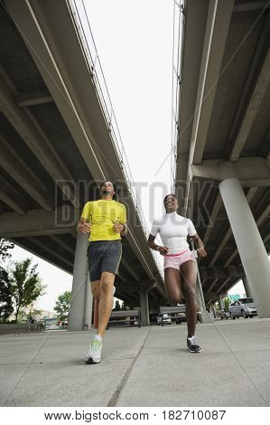 Couple running under freeway overpass