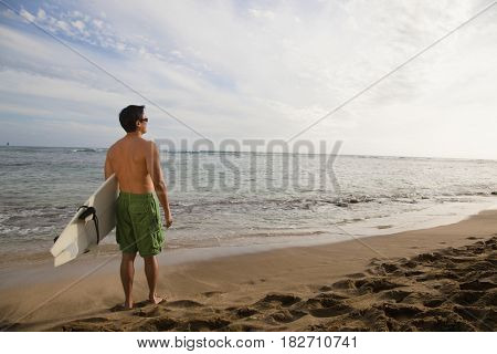 Japanese man holding surfboard on beach