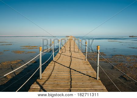 Pier in the Red sea in resort. Summer vacation on Red sea. View at a clear sea with turquoise water in windless conditions. Summer vacation at a sea coastline in an exotic country.