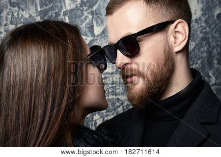 Close-up portrait of a stylish young people in sunglasses looking to each other. Beauty, fashion. Optics style. Love concept.