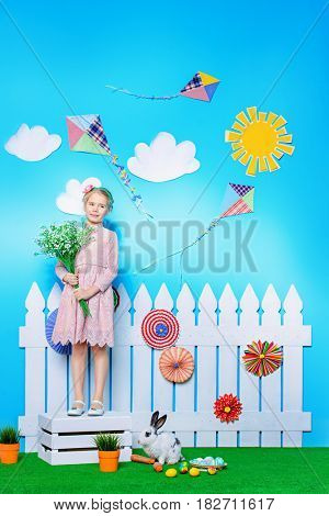 Cute happy little girl standing with Easter Bunny in spring decorations. Easter Bunny and painted eggs. Kid's fashion.