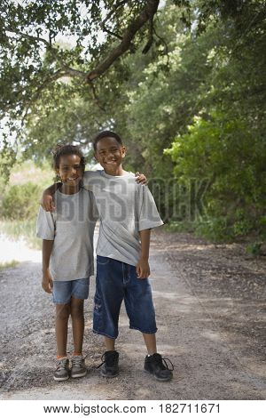 African boy and girl hugging on dirt road
