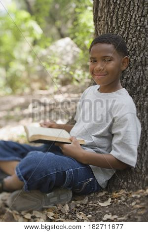 African boy reading book against tree
