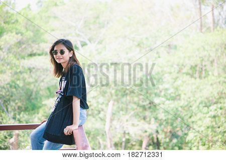 Beautiful Asia woman travelerholds in hand sunglasses holidays travel vacation and happiness concept - beautiful woman in sunglasses