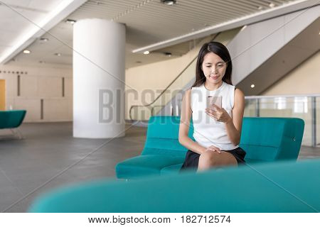 Young woman using cellphone at university hall
