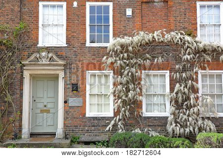 ROCHESTER, UK - APRIL 14, 2017: Exterior facade of a house  with a colorful brick wall and Spring colors