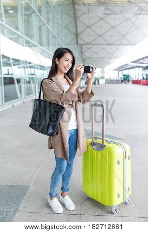 Young Woman taking photo by camera with her luggage in airport