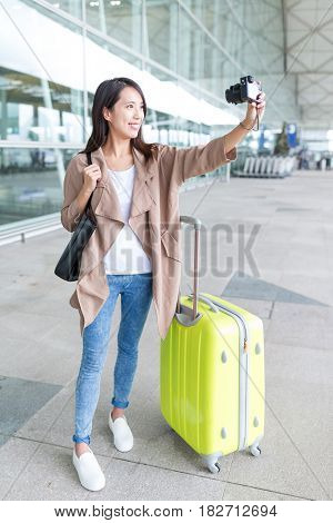 Woman taking selfie by camera in Hong Kong airport