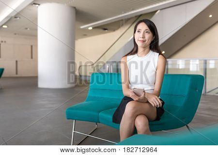 Woman looking far away and sitting at university hall