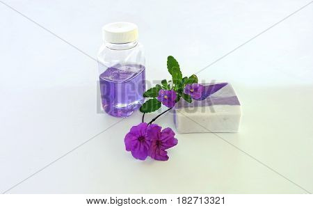 Bar and gel of lavender soap with mauve flowers on white background
