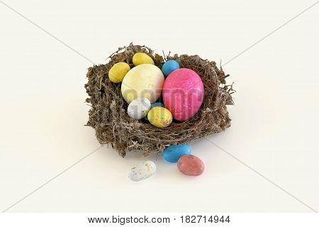 Easter eggs of different colors and sizes in a nest