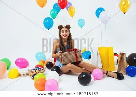 Pretty girl in fancy dress looks surprised holding big present box with red bow
