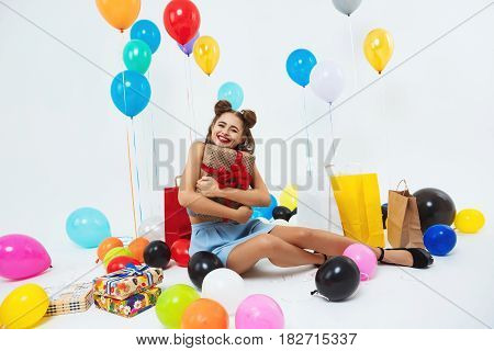 Young happy woman hugging presents sitting on floor after big bright celebration. Party concept