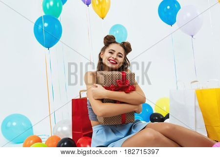 Closeup portrait of smiling girl hugging big present box with red bow, sitting on floor