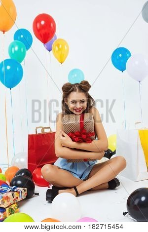 Charming woman sits in lotus position on floor in living room, holding big gift box