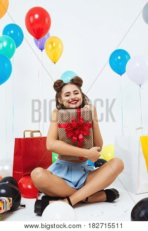 Happy woman holding big gift box with red bow. Sitting on white background in room