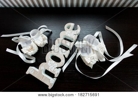 Baby shoes for a girl an home sign on background