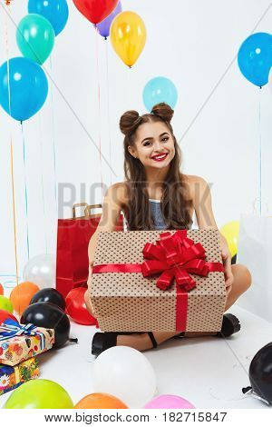 Beautiful teenager in fancy clothing showing huge present box, sitting on floor with birthday gifts