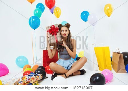 Funny girl in fashion outfit figuring out what is in big gift box, looking surprised