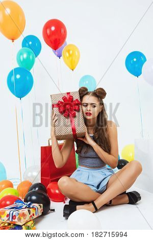 Portrait of attractive cheerful girl guessing what it is in present box, sitting in bedroom