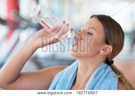 Fitness woman. Beautiful young girl in the gym on the treadmill drinking water. Fatigue, hand in head, wipes sweat.