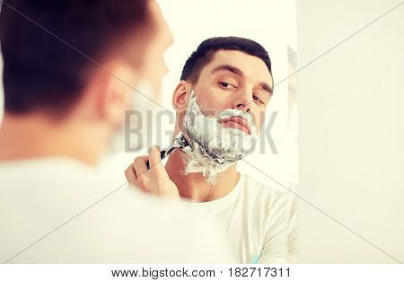 beauty, hygiene, shaving, grooming and people concept - young man looking to mirror and shaving beard with manual razor blade at home bathroom