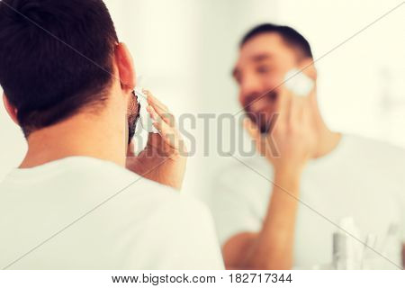 beauty, shaving, grooming and people concept - close up of man applying shaving foam to face and looking to mirror at home bathroom
