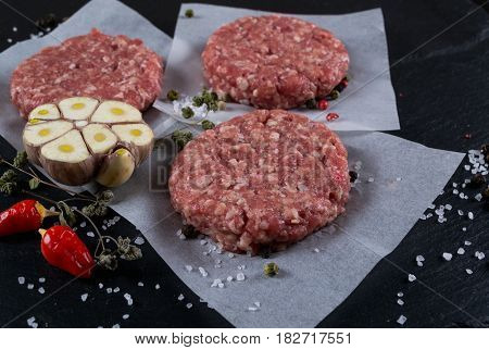 Fresh raw meat burger cutlet on the black slate board with herbs and spices for background.Top view . Selective focus.