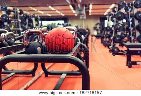 fitness, sport, exercising, weightlifting and bodybuilding concept - close up of kettlebell and medicine ball with sports equipment in gym