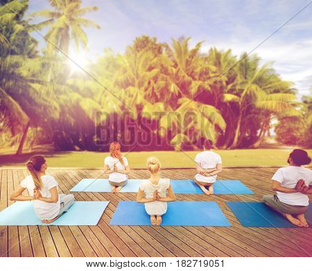 fitness, yoga, meditation and sport concept - group of people exercising in reverse prayer pose over natural background with palm trees