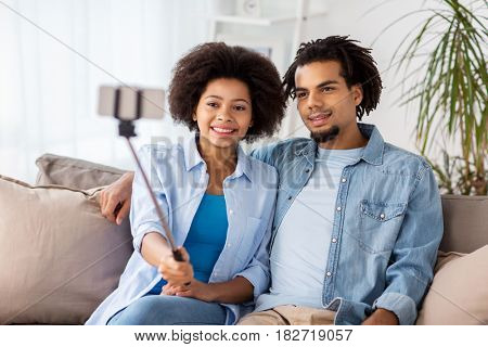 family, technology and people concept - happy couple with smartphone and selfie stick taking picture at home