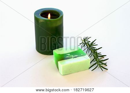 Bar soap rosemary with green candle and sprig of rosemary on white background