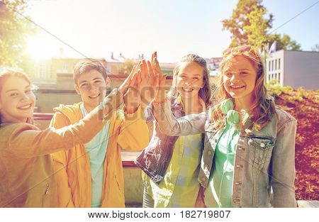 education, high school, friendship, gesture and people concept - group of happy teenage students or friends making high five outdoors